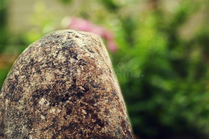 Een grote steen op een groene aardachtergrond royalty-vrije stock afbeeldingen