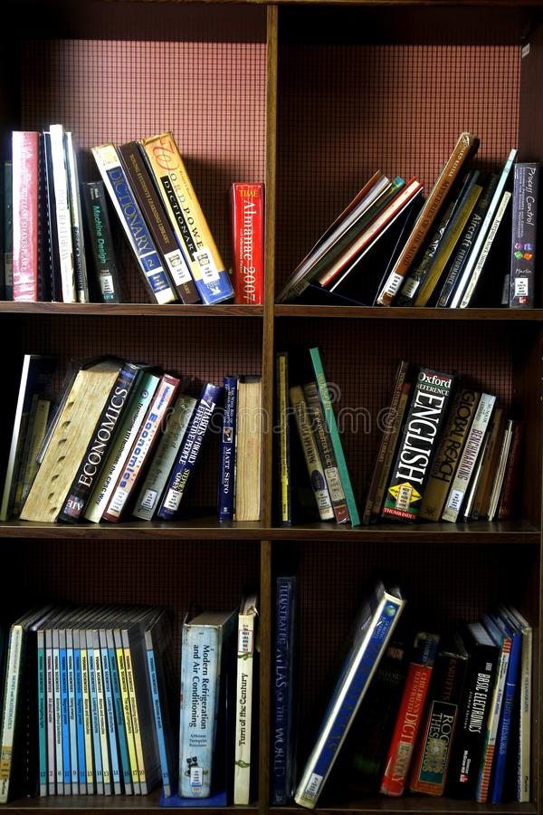 Een grote verscheidenheid van boeken op houten planken binnen een bibliotheek stock foto