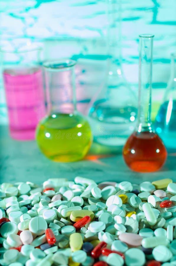 Een grote verscheidenheid van geneeskrachtige pillen op de achtergrond van de reageerbuizen en de flessen royalty-vrije stock afbeeldingen