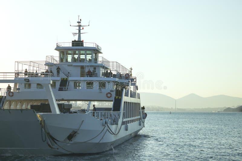 Een grote witte veerboot drijft weg in de afstand Watersleep stock afbeeldingen