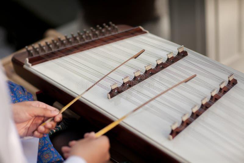 Een hakkebord dat Thais traditioneel muziekinstrument Mens die gehamerd hakkebord met houten hamers spelen stock afbeeldingen