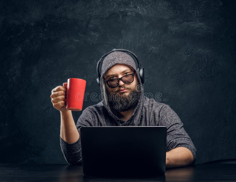 Een hakker zit achter laptop en een holding een kop van koffie in een donkere ruimte en staart vastbesloten bij de camera stock foto