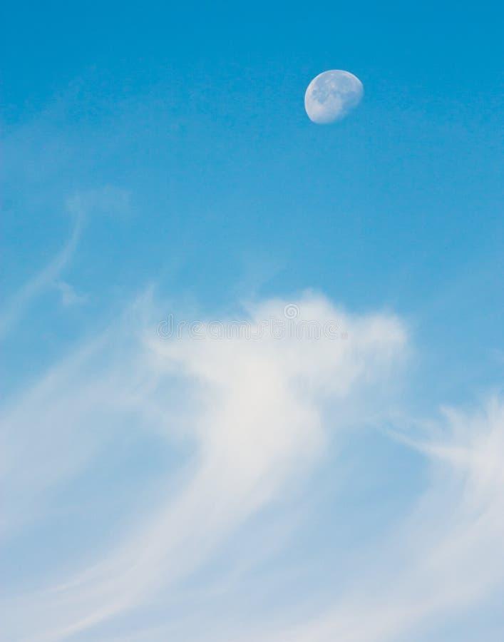Een halve maan die in de hemel boven wispy cirrus berijden betrekt stock foto's