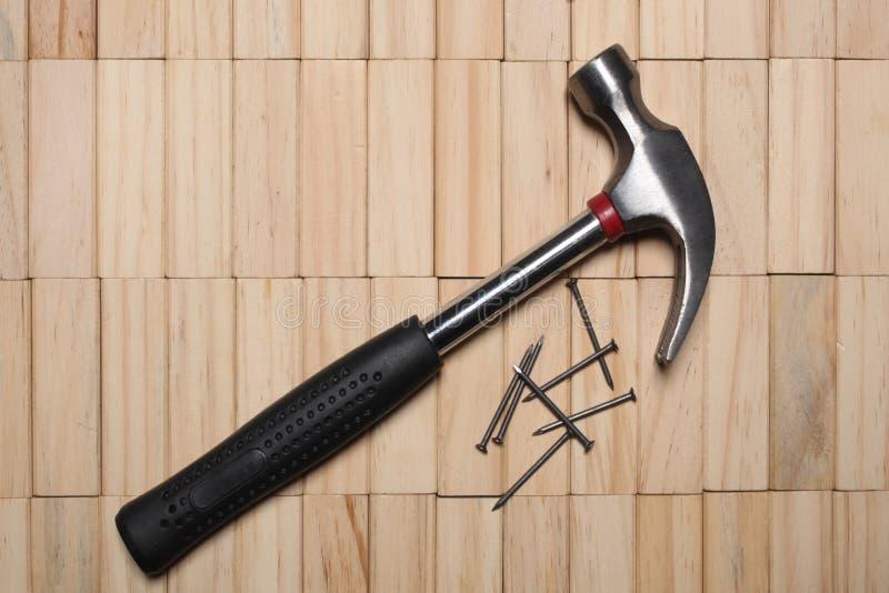 Een hamer en sommige spijkers rusten op een houten blokkenbestrating met exemplaarruimte stock foto