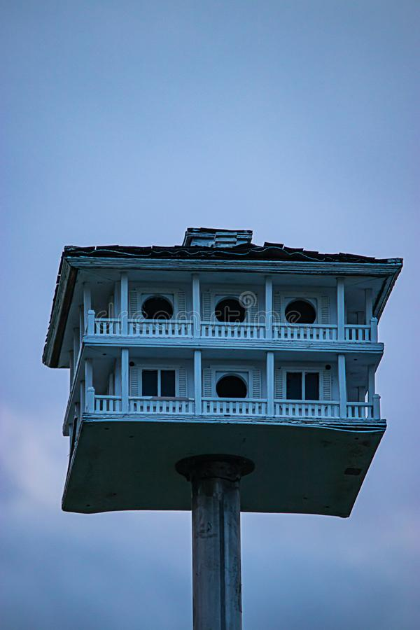 Een hand bewerkte vogelhuis met pilars een omslag rond dek en dak op een metaalpool royalty-vrije stock foto's