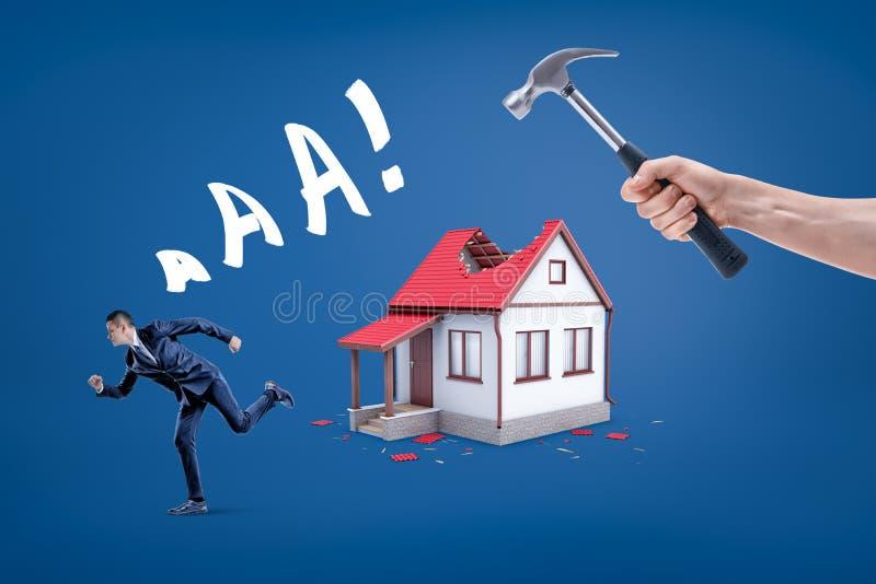 Een hand die dak van een hamer het brekende plattelandshuisje met een zakenman houden die het gillen weglopen royalty-vrije stock afbeelding