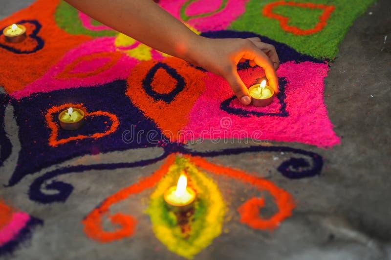 Een hand die een lamp op een mooie en kleurrijke rangoli op Diw zetten royalty-vrije stock afbeelding