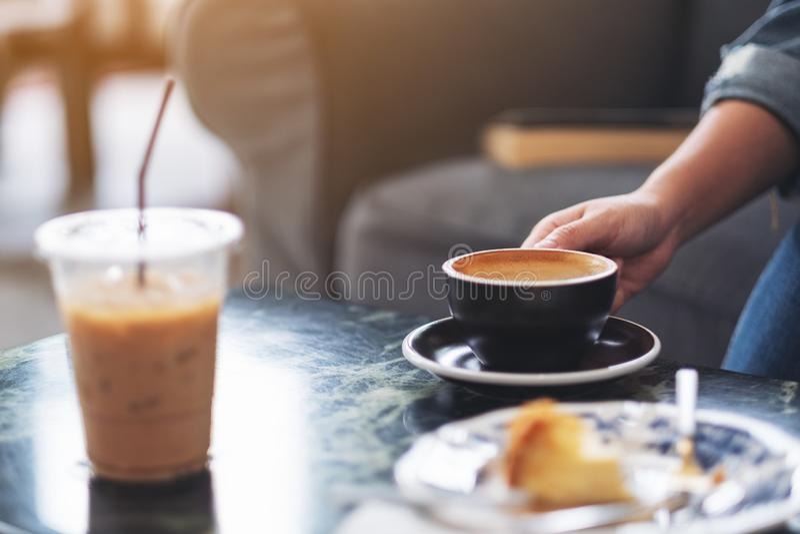 Een hand die een kop van hete koffie met plastic kop en dessert op lijst in koffie houden royalty-vrije stock foto