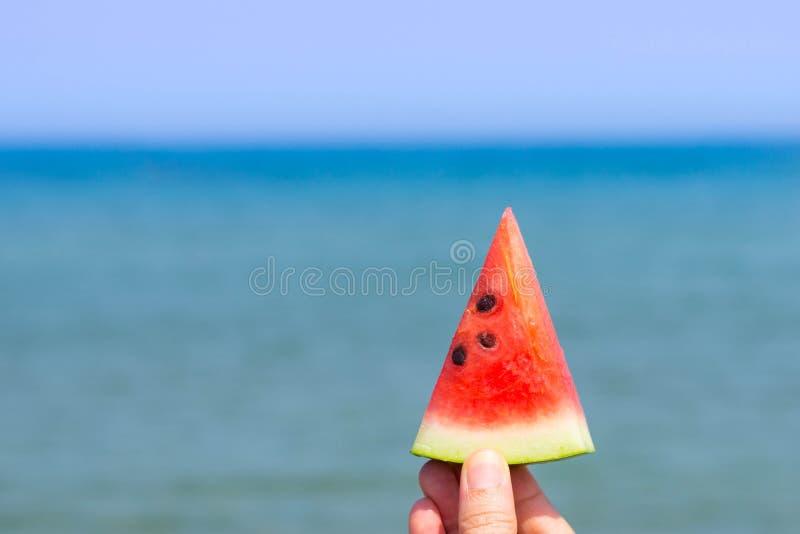 Een hand die een plak van watermeloen op het strand met blauwe overzees op de achtergrond houden royalty-vrije stock afbeelding
