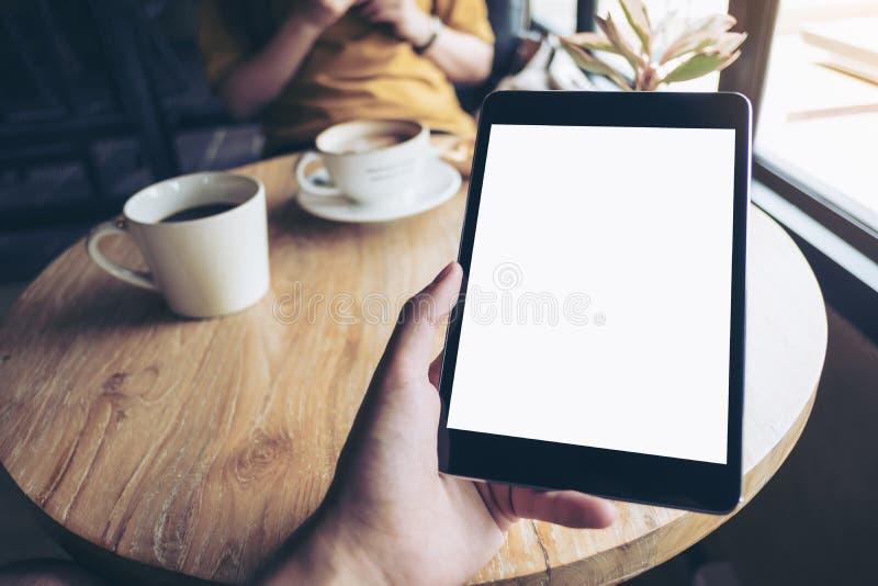 Een hand die zwarte tabletpc met het witte lege scherm op houten lijst met vrouw houden die mobiele telefoon in backgroun met beh stock afbeeldingen