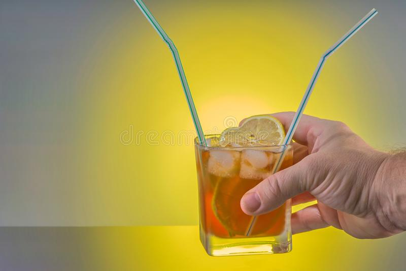 Een hand houdt een cocktail met twee buisjes Concept vriendschap, liefde en wederzijds begrip stock foto's