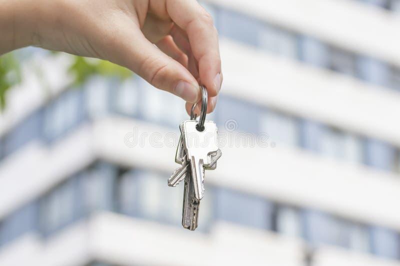 Een hand houdt de sleutels aan een gekochte flat tegen de achtergrond van een gebouw met meerdere verdiepingen royalty-vrije stock afbeelding