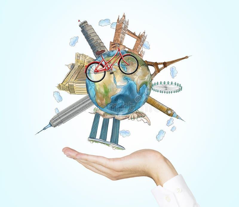 Een hand houdt een bol met de beroemdste plaatsen in de wereld Een model van fietskruisen van de bol Een concept het reizen royalty-vrije stock afbeelding