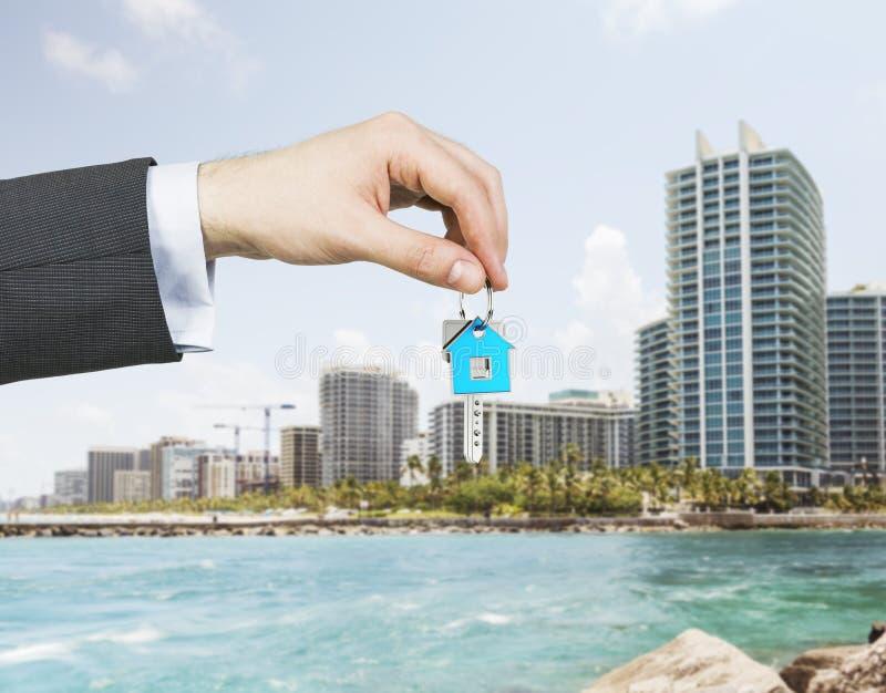 Een hand houdt een sleutel van het nieuwe huis Een concept onroerend goedagentschap stock fotografie