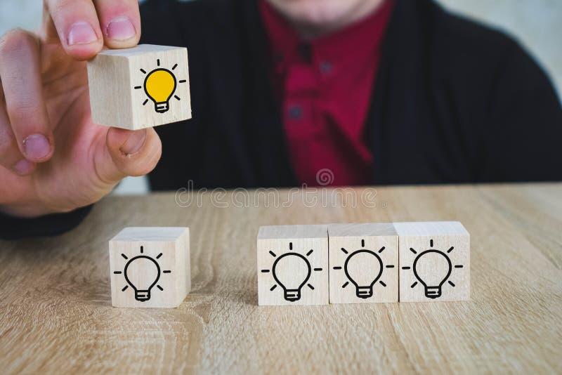 een hand houdt een kubus met een brandende lamp wanneer alle andere lampen worden gedoofd, die het Nieuwe Idee, de concepten van  royalty-vrije stock foto