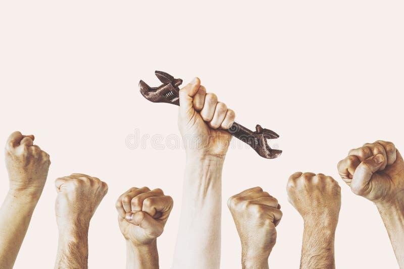 Een hand houdt een moersleutel, het concept van de Dag van de Arbeidfotografie, verscheidene ingenieursconcept stock foto