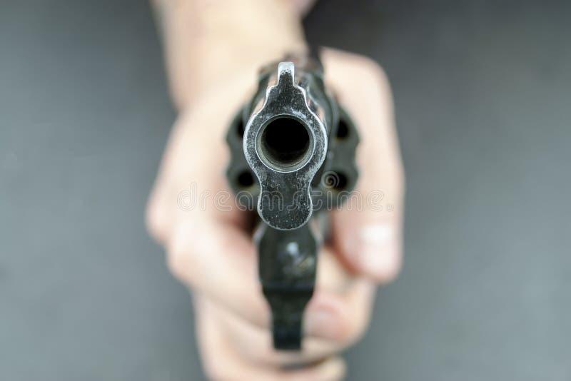 Een hand houdt een revolver, met vat dat de camera onder ogen ziet stock foto