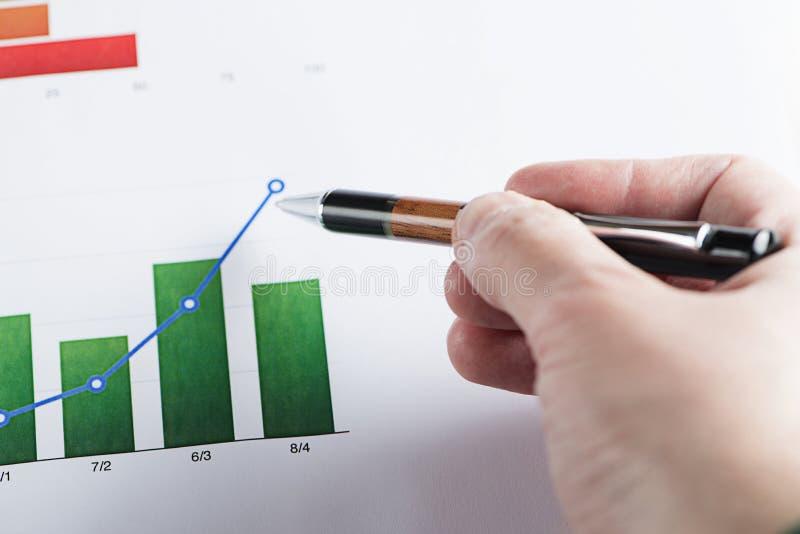 Een hand met een pen die op financiën kleurrijke grafiek richten royalty-vrije stock afbeeldingen