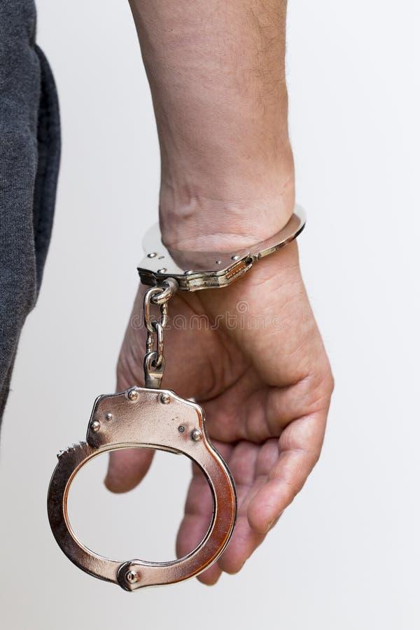 Een hand met geïsoleerd handcuffs stock fotografie