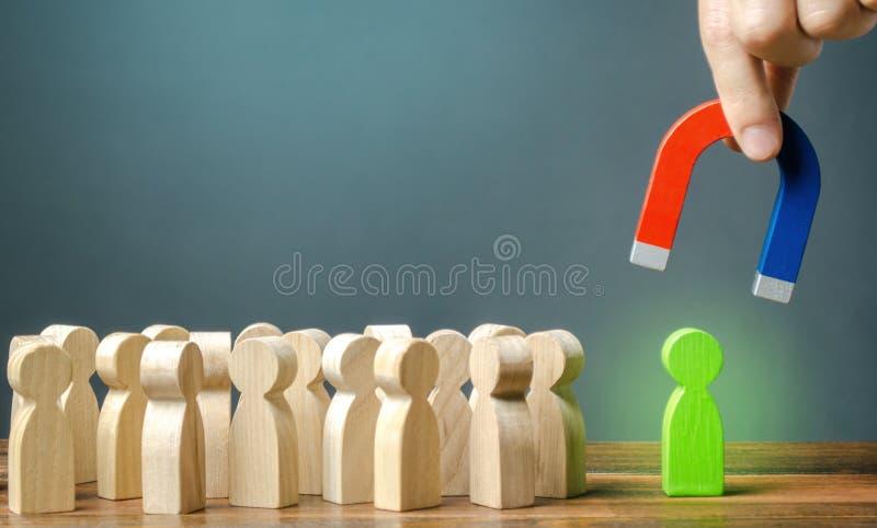 Een hand met een magneet probeert om een groen cijfer van een persoon uit een menigte te trekken Het aanwerven van nieuwe arbeide stock foto's