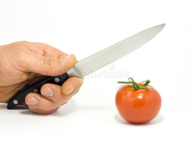 Een hand met mes en tomaat royalty-vrije stock fotografie