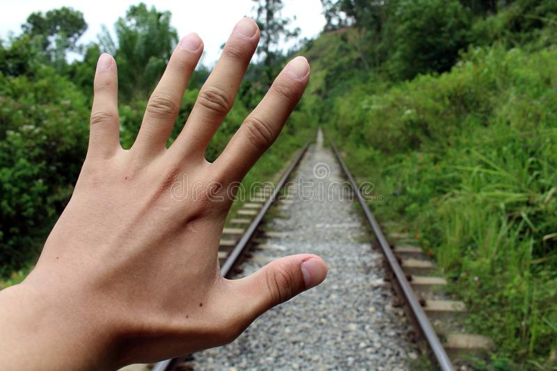 Een hand probeert om de trein komst tegen te houden stock afbeeldingen