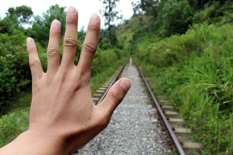 Een hand probeert om de trein komst tegen te houden stock afbeelding