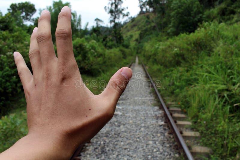 Een hand probeert om de trein komst tegen te houden royalty-vrije stock afbeeldingen