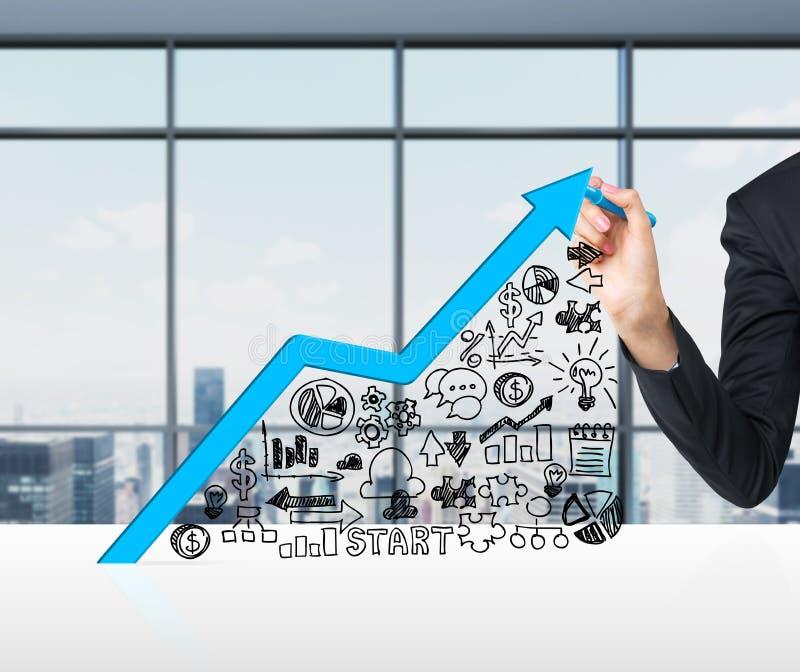 Een hand trekt een het groeien blauwe pijl als concept het succes in zaken stock afbeeldingen