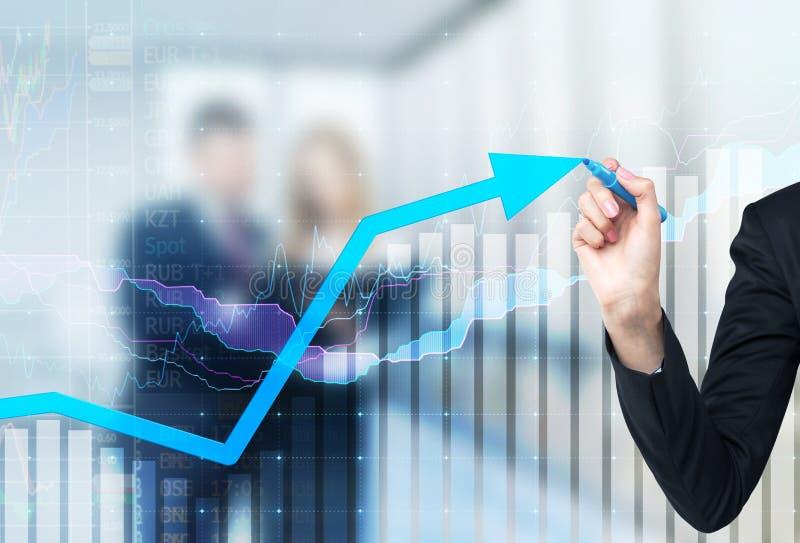 Een hand trekt een het groeien pijl op de glaspuinkegel, Blauwe donkere achtergrond met financiële grafieken stock foto's