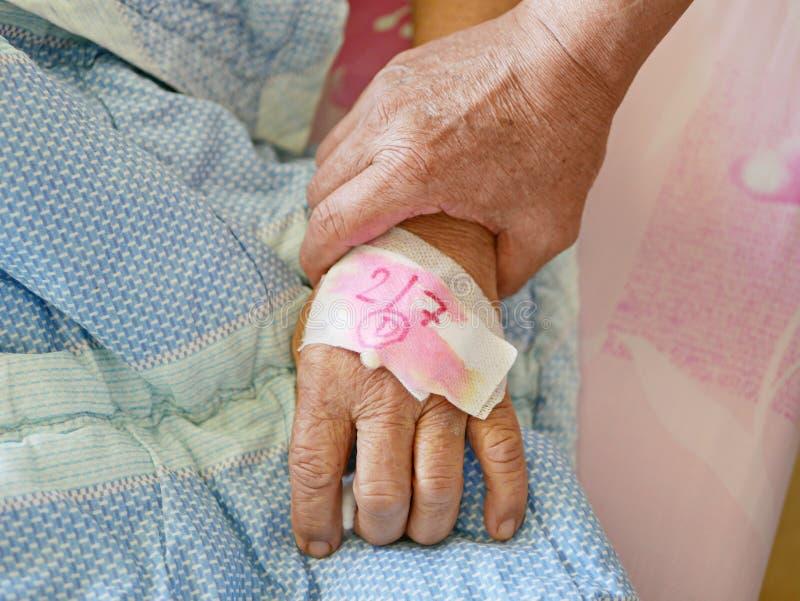 Een hand van een oude mens die een hand van een zieke oude dame houden royalty-vrije stock foto