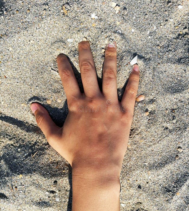 Een hand van vrouw over het zand van een Spaans strand wordt gesteld dat stock fotografie
