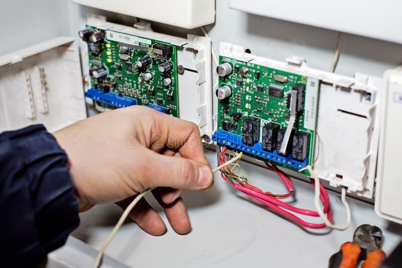 Een hand verbindt de draad met de spaanplaat Reparatie, onderhoud en aanpassing van materiaal door een gekwalificeerde technicus royalty-vrije stock afbeelding