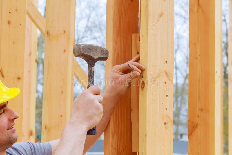 Een handarbeider die van de bouwdag houten stralen draagt Authentieke bouwvakker op een daadwerkelijke bouwwerf stock afbeelding