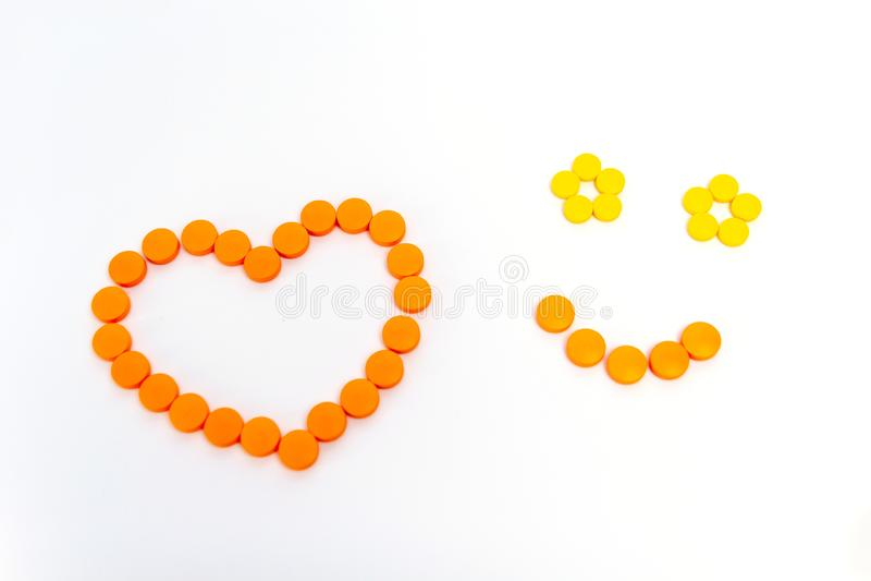 Een hart en een glimlach zijn door oranje die pillen op witte achtergrond worden geïsoleerd Het concept van de geneeskunde royalty-vrije stock foto