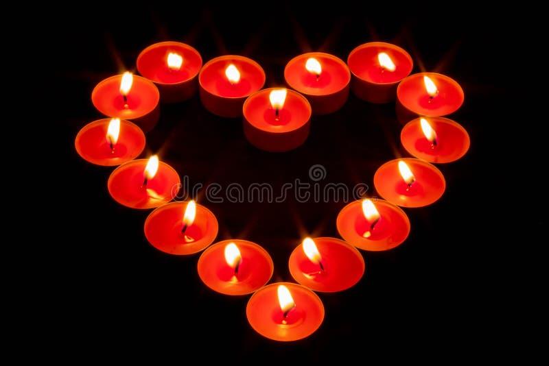 Een hart met rode kaarsen wordt gemaakt die stock fotografie