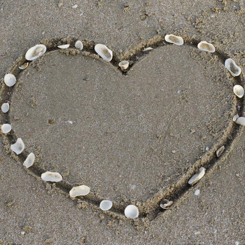 Een hart op het zand in het strand stock foto's