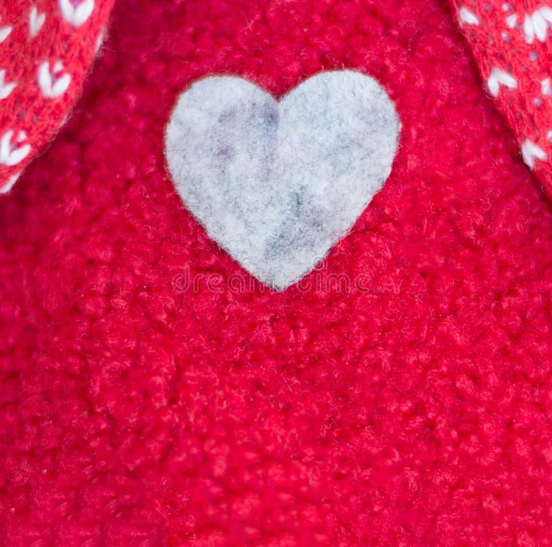 Een hart in een rode wollen sweater wordt genaaid die stock afbeeldingen