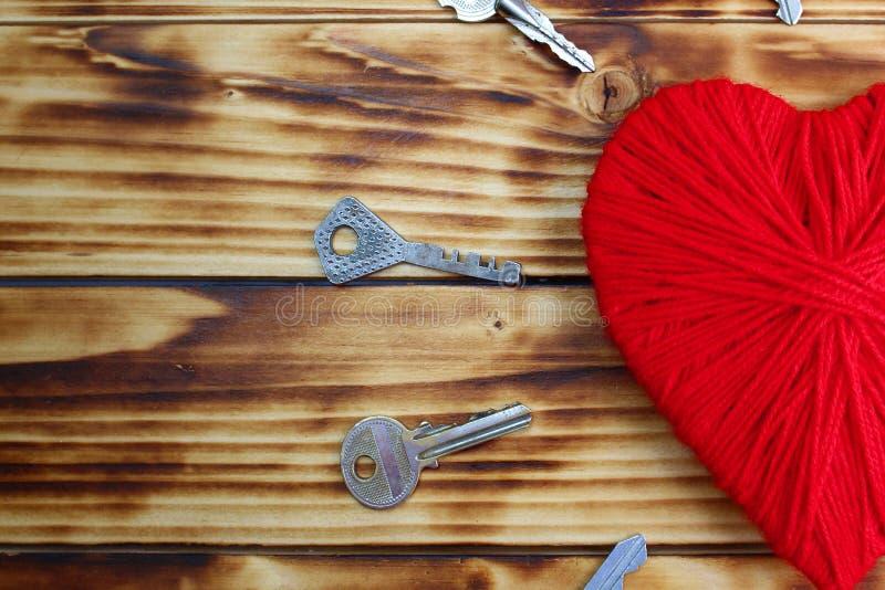 Een hart van rode kleur van garen en de sleutels liggen rond het royalty-vrije stock fotografie