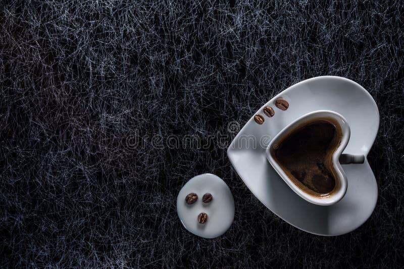 Een hart vormde koffiekop met koffiebonen en morste melk op een zilveren keuken achtergrondlijstbovenkant stock foto's