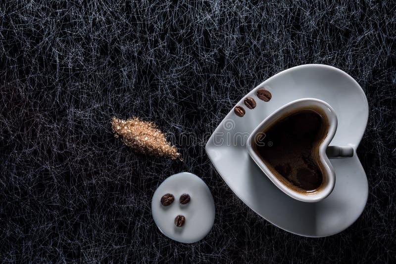 Een hart vormde koffiekop met koffiebonen, gemorste melk en bruine suiker op een zwarte achtergrond met zilveren voering royalty-vrije stock foto's