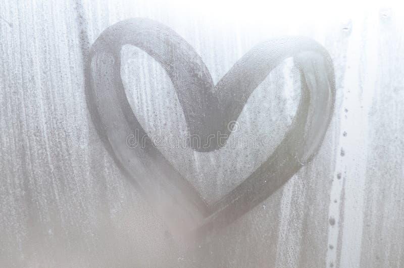 Een hart-vormige die tekening door een vinger op a wordt getrokken misted glas in regenachtig weer royalty-vrije stock foto's