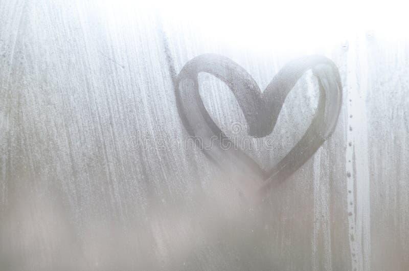 Een hart-vormige die tekening door een vinger op a wordt getrokken misted glas in regenachtig weer stock afbeeldingen