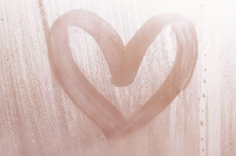 Een hart-vormige die tekening door een vinger op a wordt getrokken misted glas in regenachtig weer stock foto's