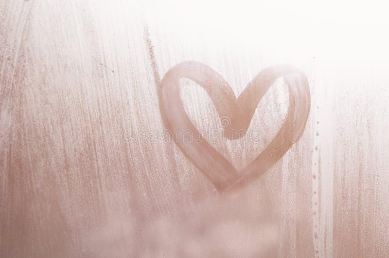Een hart-vormige die tekening door een vinger op a wordt getrokken misted glas in regenachtig weer stock afbeelding