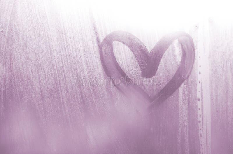 Een hart-vormige die tekening door een vinger op a wordt getrokken misted glas in regenachtig weer stock foto