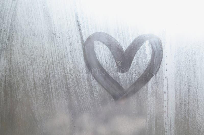 Een hart-vormige die tekening door een vinger op a wordt getrokken misted glas in regenachtig weer royalty-vrije stock foto