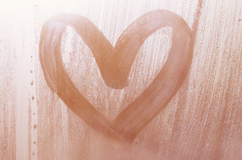 Een hart-vormige die tekening door een vinger op a wordt getrokken misted glas in regenachtige weathe royalty-vrije stock foto's