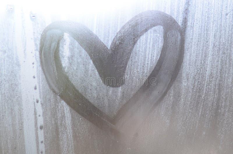 Een hart-vormige die tekening door een vinger op a wordt getrokken misted glas in regenachtige weathe stock fotografie