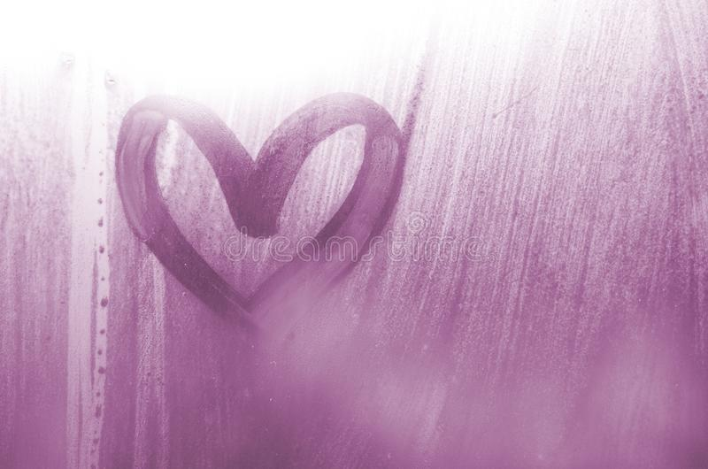 Een hart-vormige die tekening door een vinger op a wordt getrokken misted glas in regenachtige weathe stock afbeelding